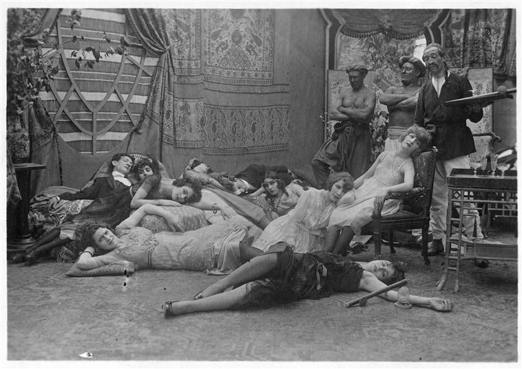 Women on the floor smoking opium and three eunuchs watching them: Broquin, Max the Eunuch and Footitt